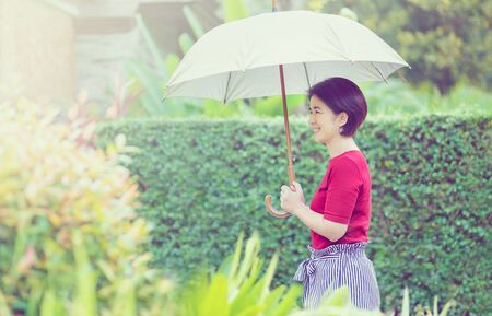 Middle age Asian woman holding umbrella in strong sunlight Imagens