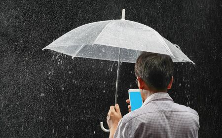 Middle aged asian male holding his umbrella and phone under rain in night time Imagens
