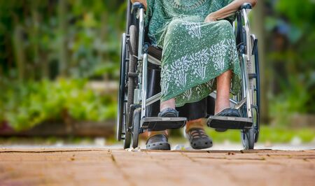 Elderly woman on wheelchair at home with daughter take care