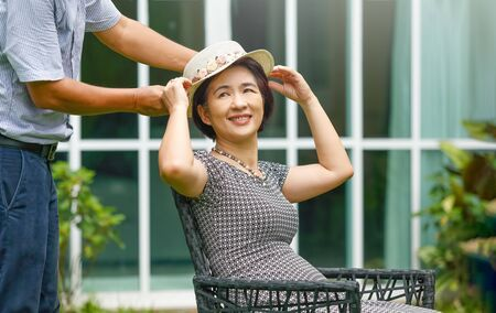 Asian middle aged couple sitting relax in backyard and putting on a hat to his wife Imagens