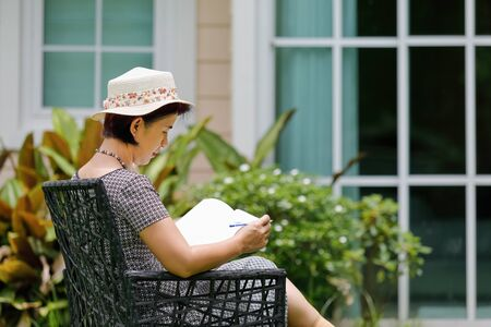 Asian middle aged female sitting relax in backyard