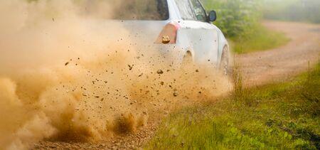 Gravel splashing from rally car drift on dirt track Stock Photo