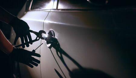 Car thief using a tool to break into a car Zdjęcie Seryjne