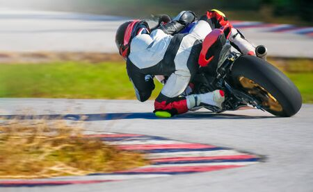 Motorcycle leaning into a fast corner on race track Фото со стока