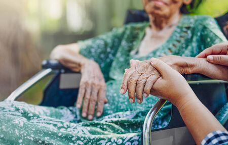 Anciana asiática en silla de ruedas en casa con hija cuidar