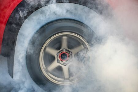 Drag racing car burns rubber off its tires in preparation for the race Archivio Fotografico