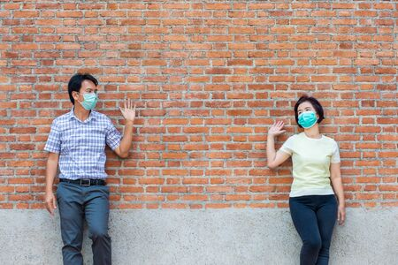 Asian middle aged people wearing mask and keep social distancing to avoid the spread of COVID-19 Stock Photo