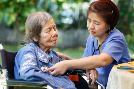 nurse checking lung of elderly woman during homecare medical