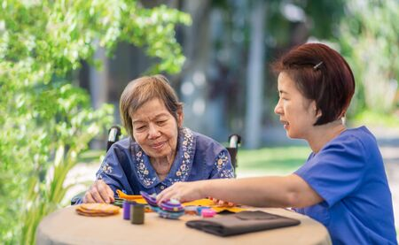 Elderly woman with caregiver in the needle crafts occupational therapy  for Alzheimer's or dementia