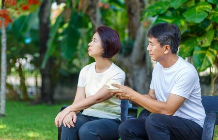 Asian middle aged male asking to make up with his wife 版權商用圖片