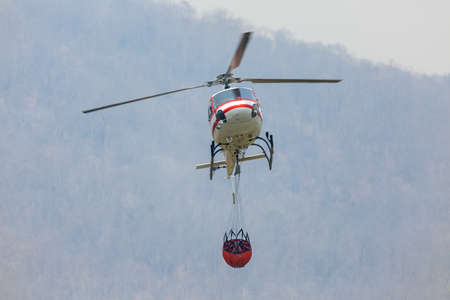 Firefighting  helicopter carrying  water bucket for extinguish forest fire,   comeback at lake to filling water
