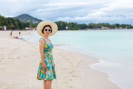 Asian middle aged woman relaxing at chaweng beach in koh samui ,Thailand.