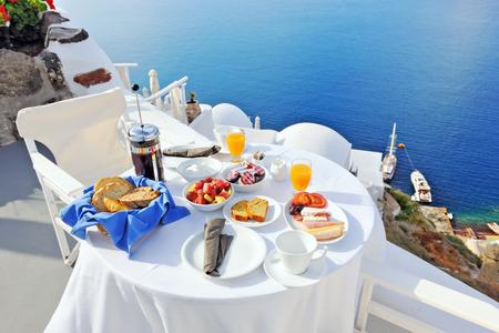 overlooking: El desayuno en una terraza con vistas al mar en Oia, Santorini, Grecia Foto de archivo