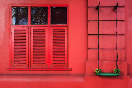 red wall and windows with green swing decorated photo