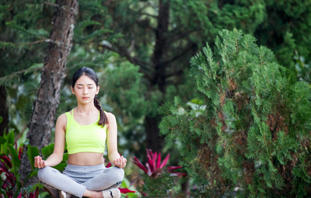 Beautiful young woman wearing neon green aerobic clothing and grey aerobics pants enjoying yoga green forest outdoors. Resting after doing yoga exercises, sitting in ardha Padmasana, Lotus pose, relaxing. Full length