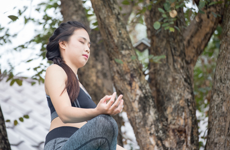 ardha: Beautiful young woman wearing black aerobic clothing enjoying yoga in green forest outdoors. Resting after doing yoga exercises, sitting in ardha Padmasana, Lotus pose, relaxing.