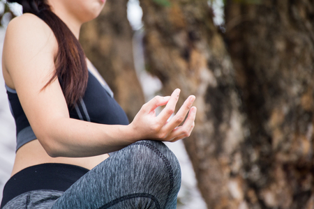 Beautiful young woman wearing black aerobic clothing enjoying yoga in green forest outdoors. Resting after doing yoga exercises, sitting in ardha Padmasana, Lotus pose, relaxing.