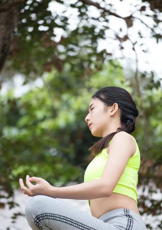 Beautiful young woman wearing neon green aerobic clothing and grey aerobics pants enjoying yoga outdoors. Resting after doing yoga exercises, sitting in ardha Padmasana, Lotus pose, relaxing. Stock Photo