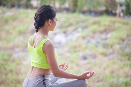 Beautiful young woman wearing neon green aerobic clothing and grey aerobics pants enjoying yoga outdoors. Resting after doing yoga exercises, sitting in ardha Padmasana, Lotus pose, relaxing. Back side Stock Photo
