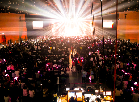 people at a night concert with orange tone of light Banco de Imagens