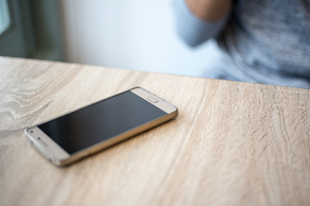 gold mobile phone on the wooden table  Banco de Imagens