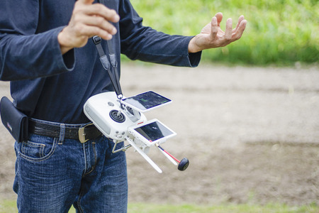 huge white remote control of drone for agriculture hanging on a man neck standing in front of the farm