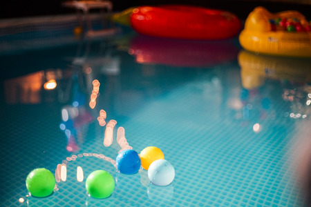 light bulb reflection and small balls on the water in night pool party Banco de Imagens
