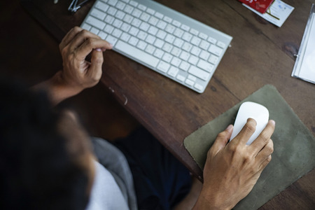 Unkown man using a white wireless mouse with keyboard on wooden table