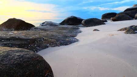Sand beach with reef and pastel sunrise sky on the morning.