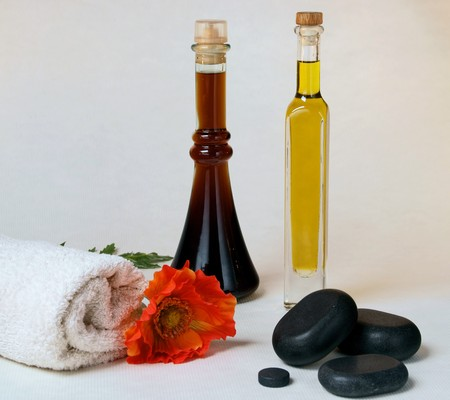 Massage oils with hot stone, towel and poppy. photo
