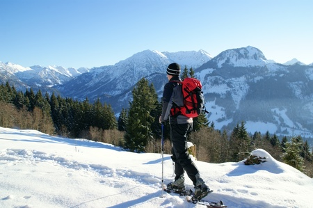 snowshoe: A man makes a snowshoe tour in a beautiful mountain landscape. Stock Photo