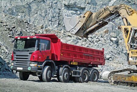 camion volteo: Volcado de camiones y excavadoras en una cantera Foto de archivo