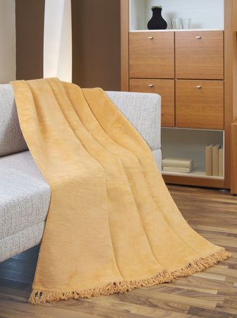 Blanket draped over a settee photo