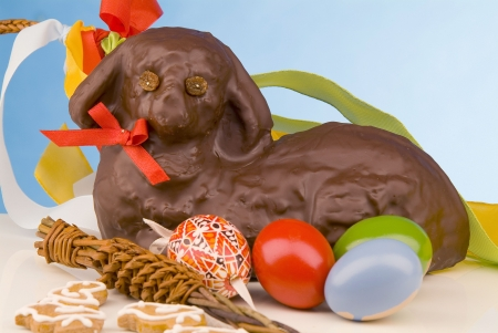 Still life of Easter lamb with chocolate icing, painted eggs and whipping cane