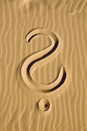 Question mark drawn in the sand photo