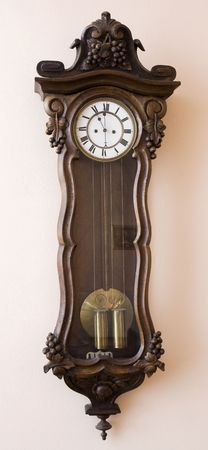 Antique clock hanging on a wall  Stock Photo