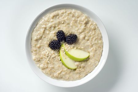 topped: Bowl of porridge topped with blackberries and apple