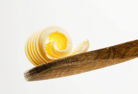 Single butter curl on a wooden spoon   photo