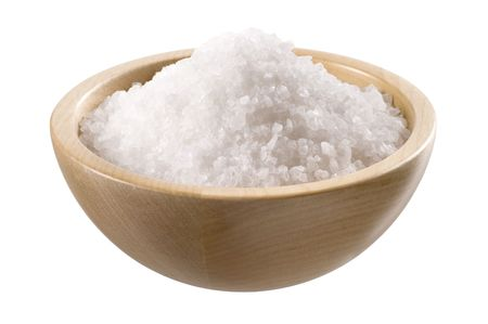 Sea salt in a wooden bowl  isolated on white photo