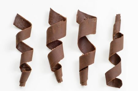 Four chocolate spirals on white  background - overhead photo