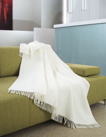 settee: White throw draped over a green settee Stock Photo