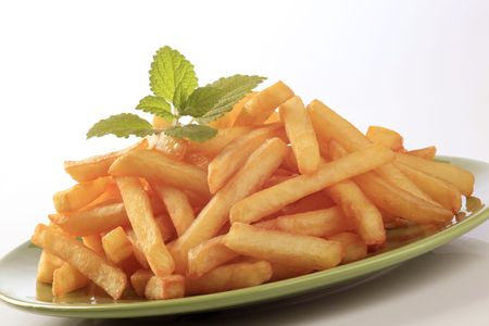 papas fritas: Mont�n de papas fritas en un plato verde Foto de archivo