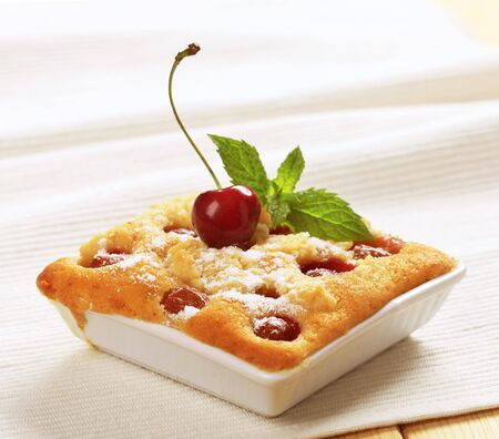 Fresly baked cherry sponge cake in a square ceramic dish photo