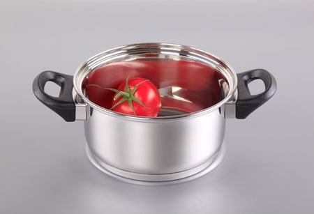 Red tomato in a shiny stainless steel pot  photo