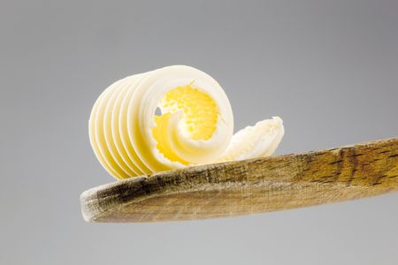 Closeup of a butter curl on a wooden spoon  Stock Photo - 5268984