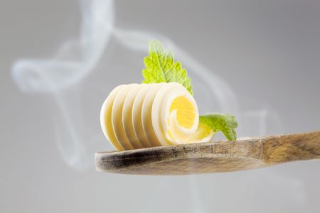 Butter curl on a wooden spoon in steam photo