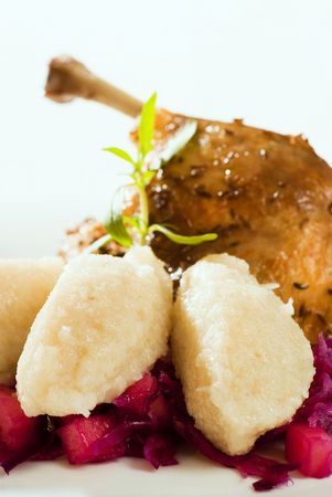 red cabbage: Roast duck and potato dumplings on red cabbage in the foreground