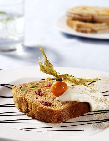 fruitcake: Slice of fruitcake topped with cream and physalis fruit
