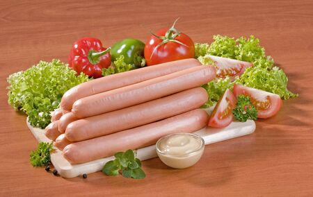 Raw sausages stacked on a cutting board photo