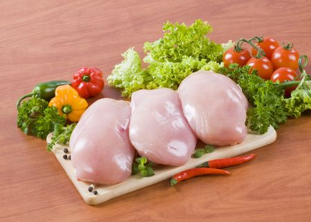 Raw chicken fillets and fresh vegetables